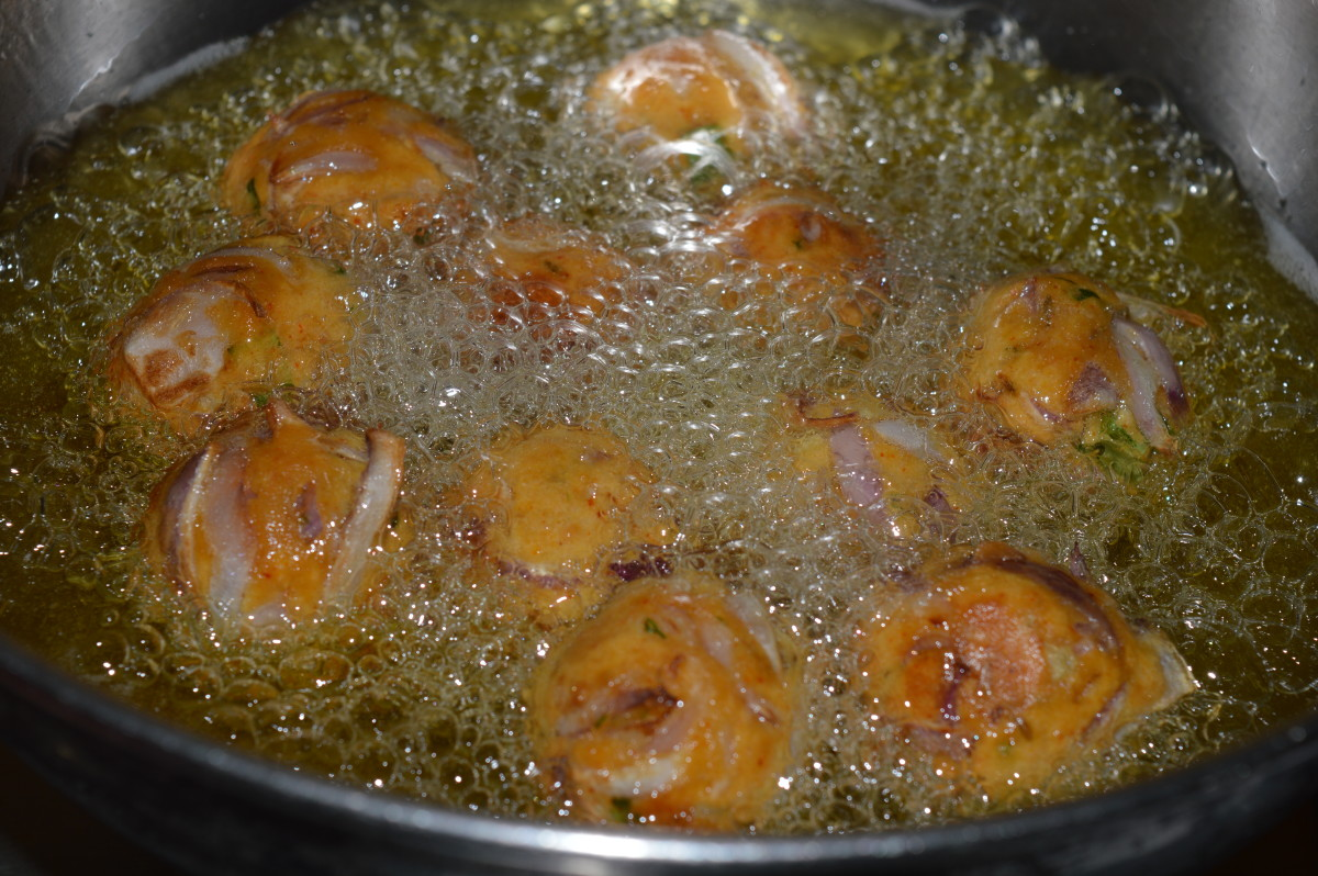 Step five: Heat oil for deep frying. Drop the balls one by one into the hot oil. Fry them on medium high fire in the beginning. Turn them occasionally. Lower the heat after 2 minutes.