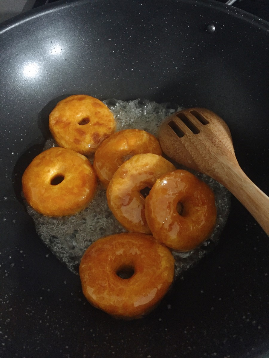 Quickly, add the donuts into the sugar syrup.