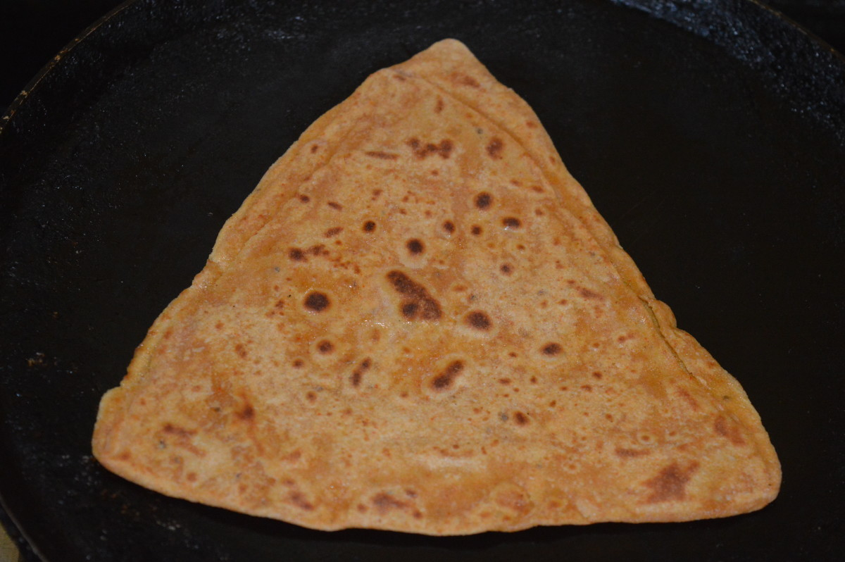 Step eleven: Remove and place it on a plate. Make all the parathas like this.