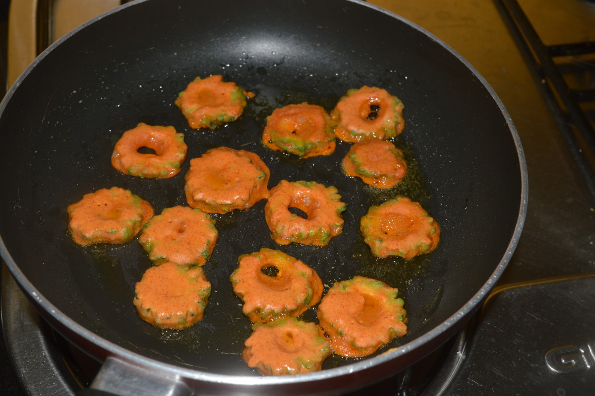 Step five: Add a teaspoon of oil on a hot non-stick pan. Place the batter coated bitter gourd slices one by one as shown in the pic. Add a few drops of oil on them.