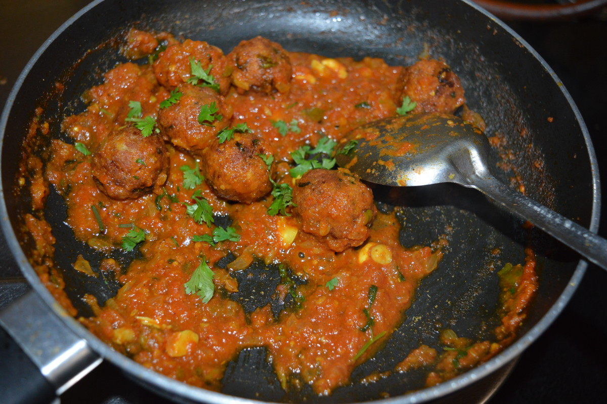 Step eleven: Add koftas. I added koftas, keeping a few for myself to eat as snacks. Mix well. Stir-cook the mix for a minute. Turn off the stove. Garnish the curry with chopped coriander leaves.