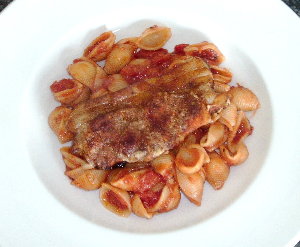 Paprika spiced pork steak is laid on conchiglie pasta