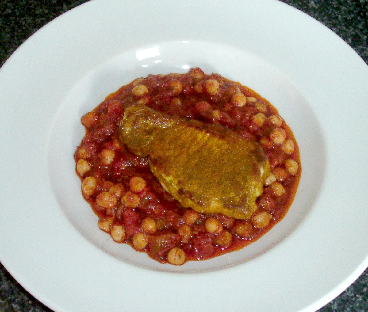 Turmeric spiced pork steak is laid on chickpeas