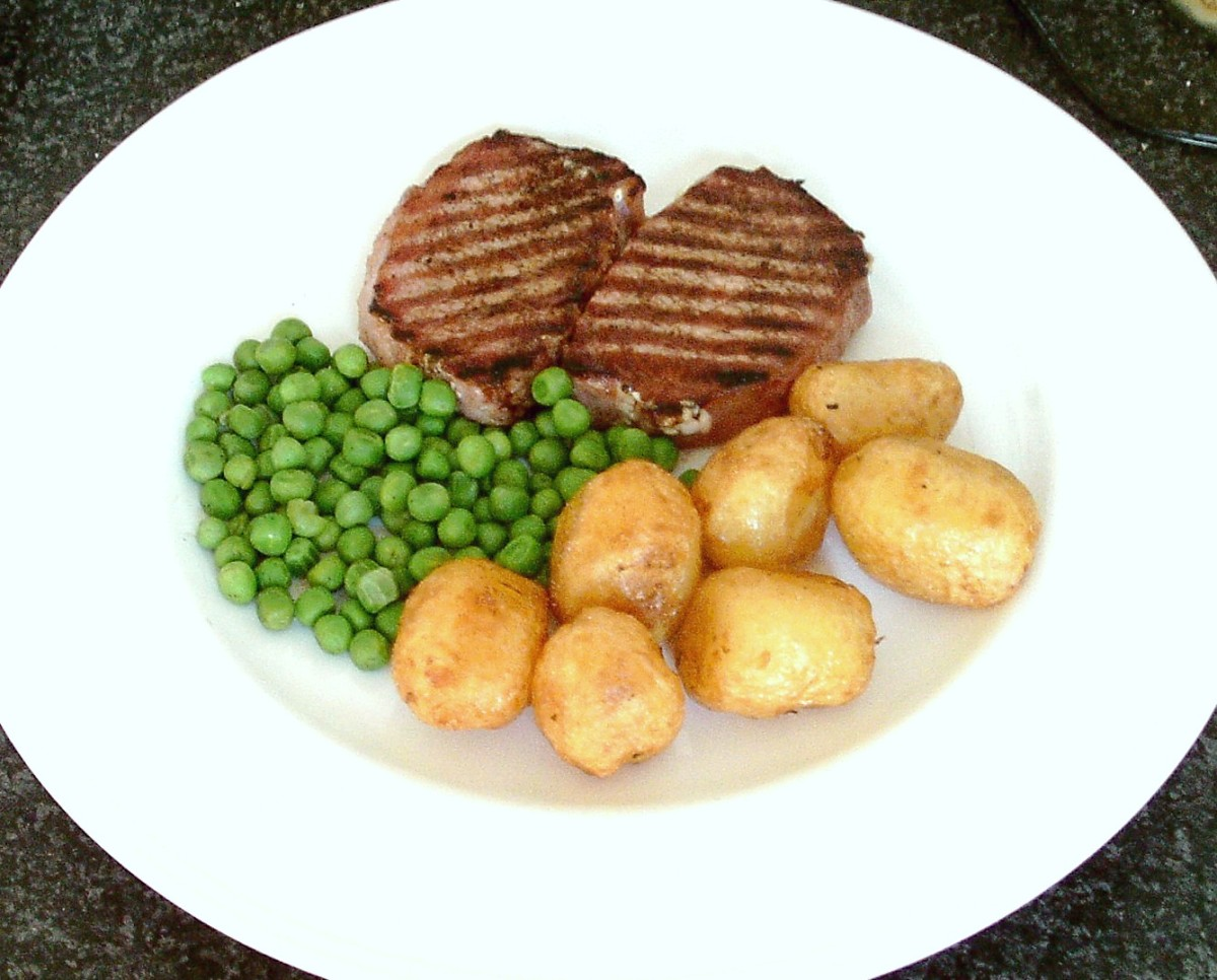 Griddled pork loin mini steaks with deep fried baby potatoes and garden peas