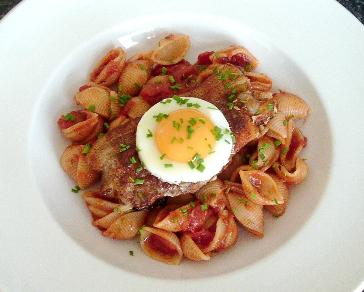 Paprika spiced fried pork steak on conchigle pasta in tomato sauce, topped by a fried egg