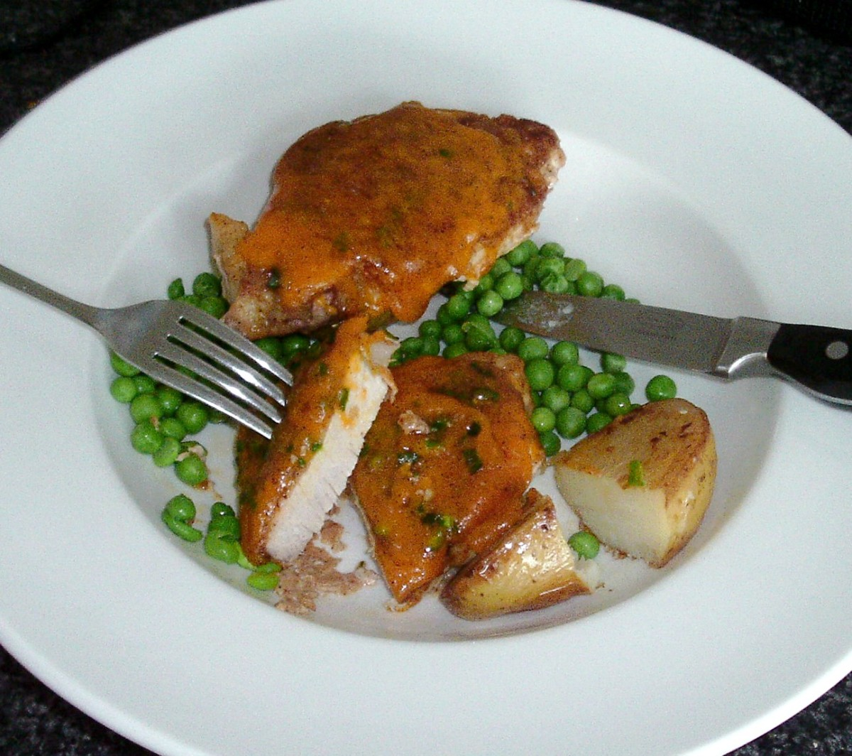 Spicy cheese crusted pork steaks served on curried fried potato with peas
