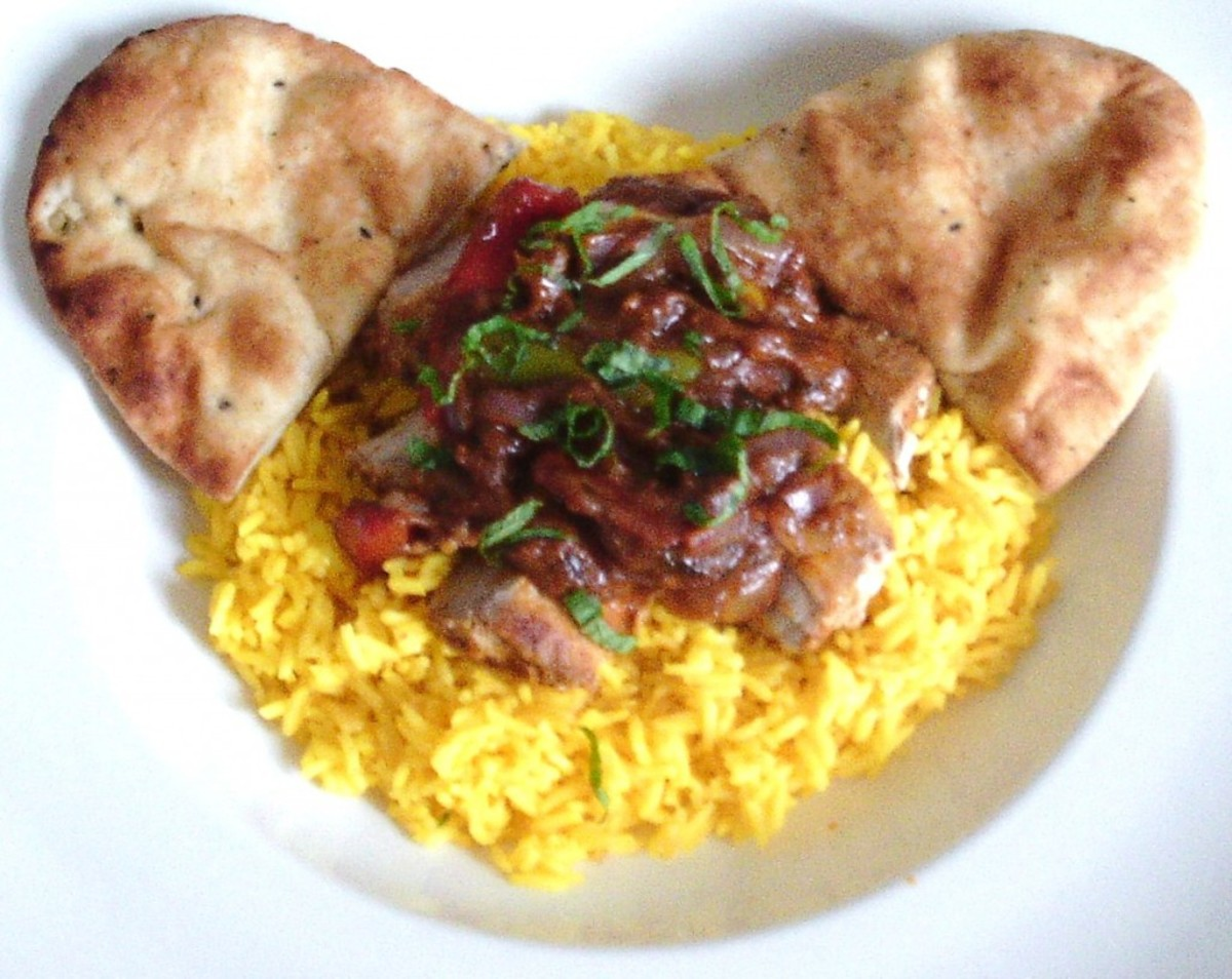 Pork steak in a vindaloo sauce is served on a bed of turmeric rice with naan bread