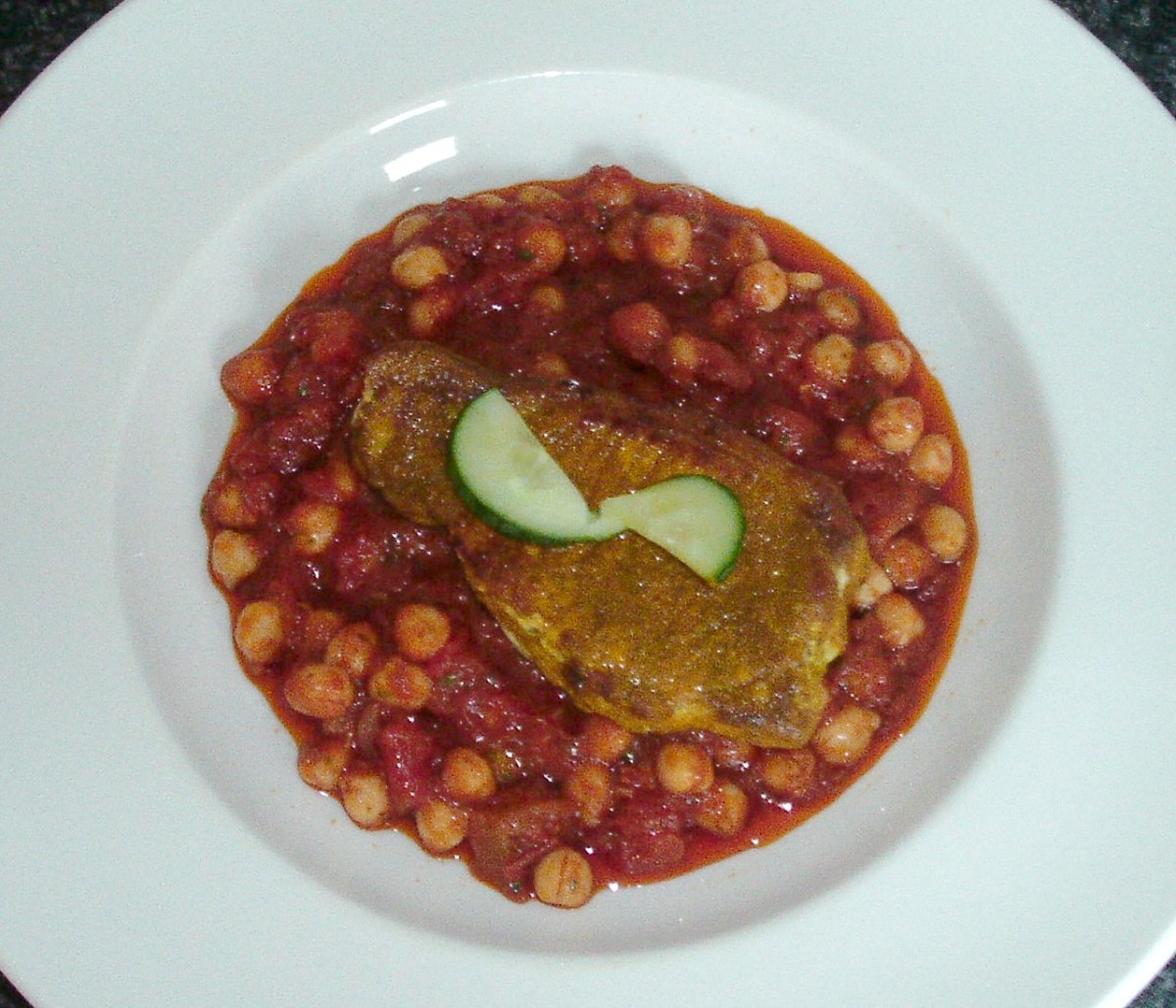 Turmeric spiced fried pork steak on bed of curried chickpeas