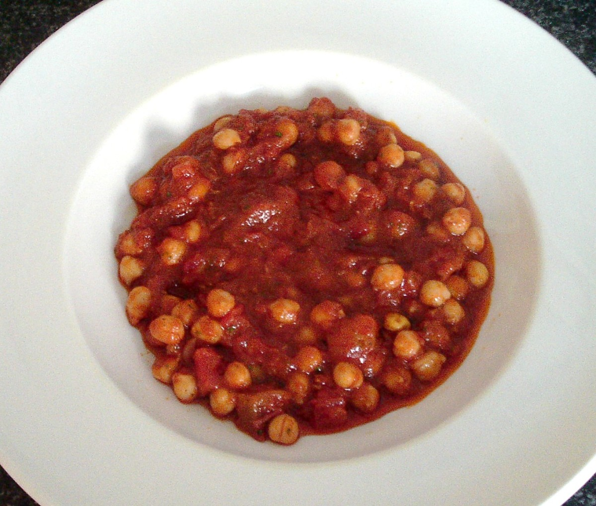 Curried chickpeas are poured in to serving plate