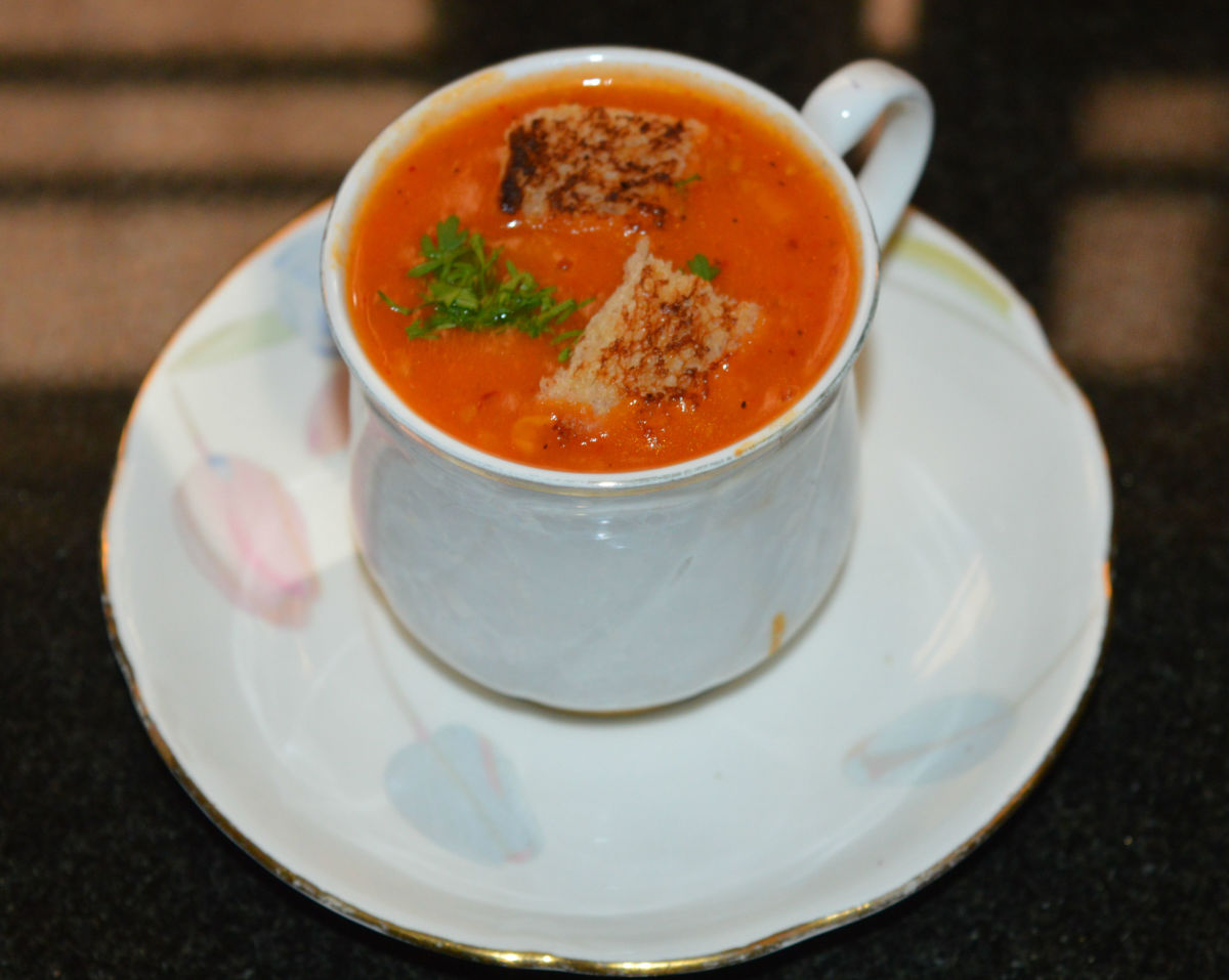 Pour the soup into 2 bowls. Garnish with roasted bread cubes and finely chopped coriander leaves. Enjoy sipping this tangy and aromatic soup!