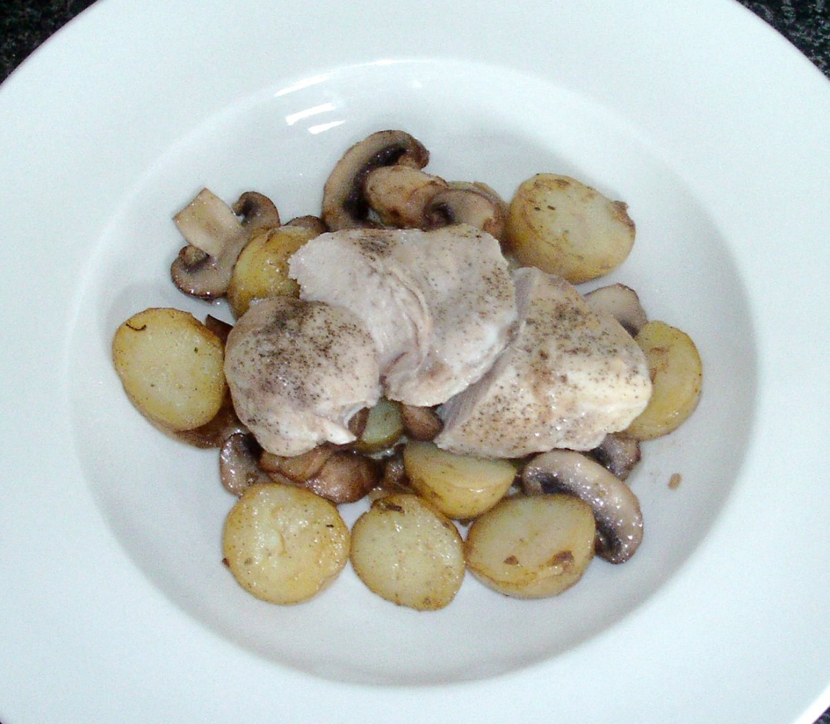 Simply baked chicken breast fillet is served on a bed of stir fried potatoes and mushrooms