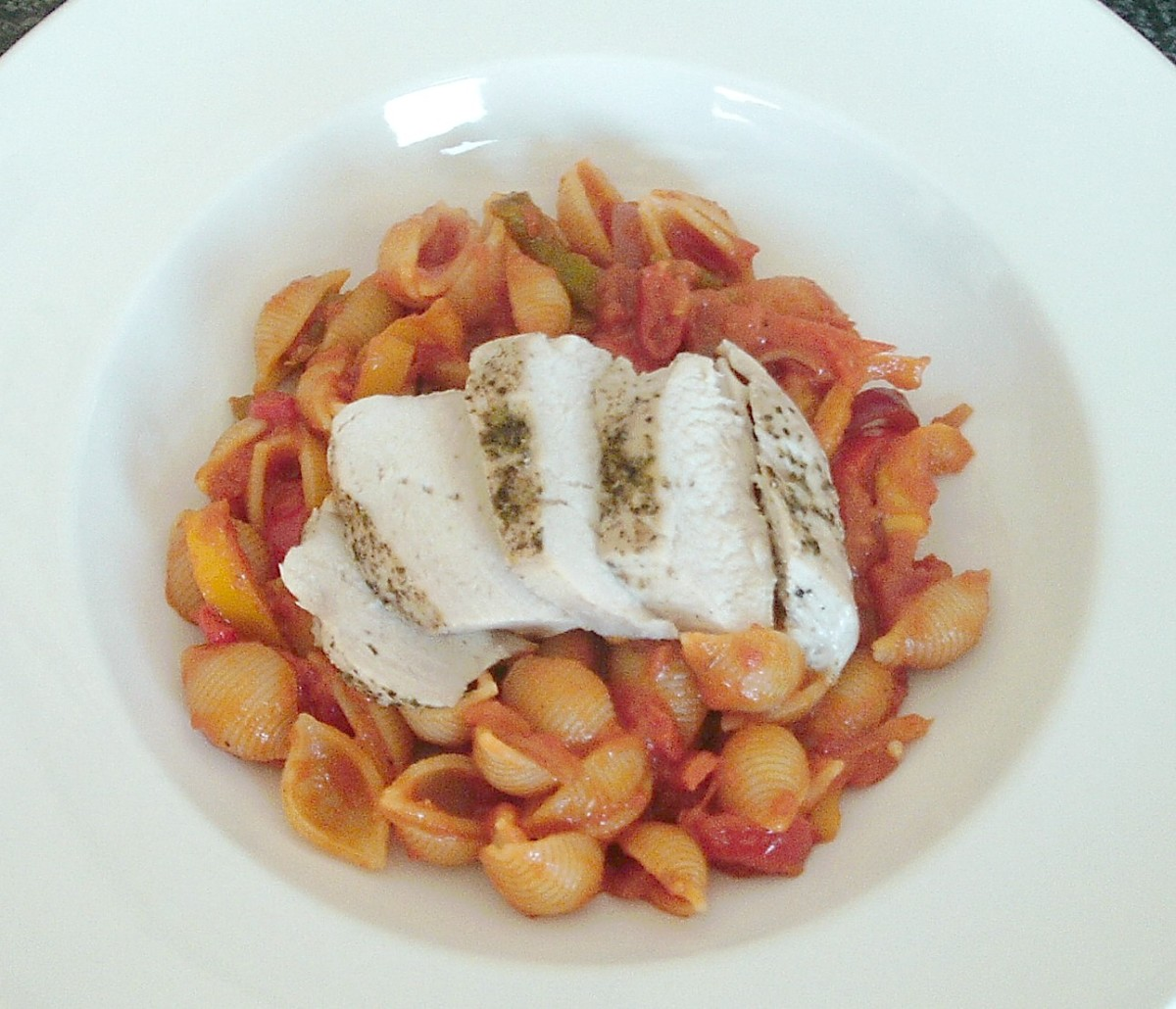 Simply baked chicken breast with herbs is served on a bed of conchiglie pasta in tomato sauce
