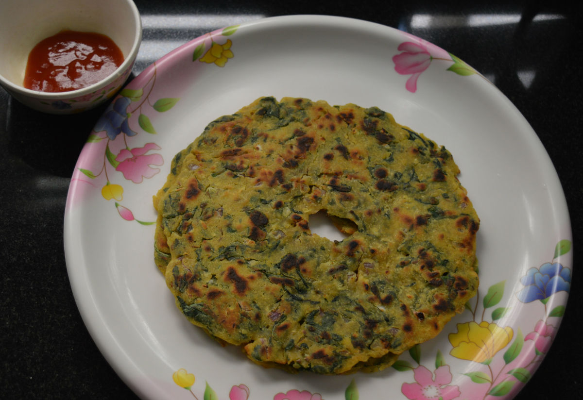 Now, palak thalipeeth or spinach pancakes are ready to eat. Serve them with tomato sauce or a cup of yogurt. Enjoy the taste.