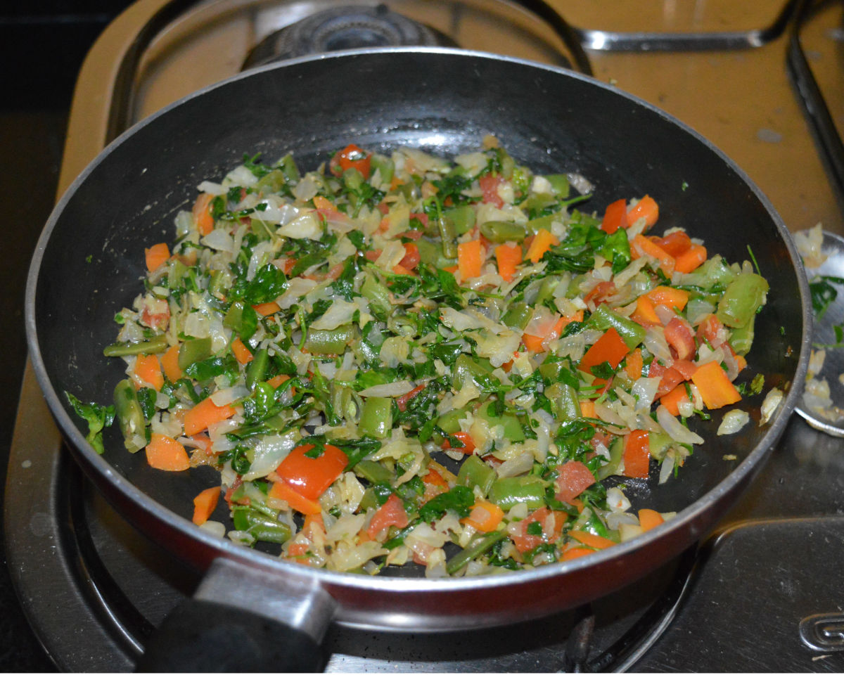 Cooking the fenugreek leaves into the veggies.