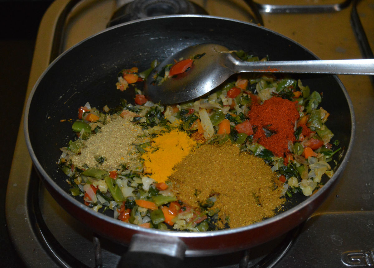 Step seven: Add all the spice powders one by one. Reduce the heat. Add sugar and remaining salt. Mix well.