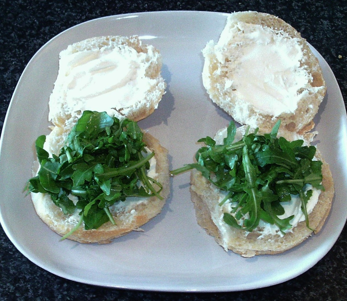 Rocket leaves laid on cream cheese spread roll bases