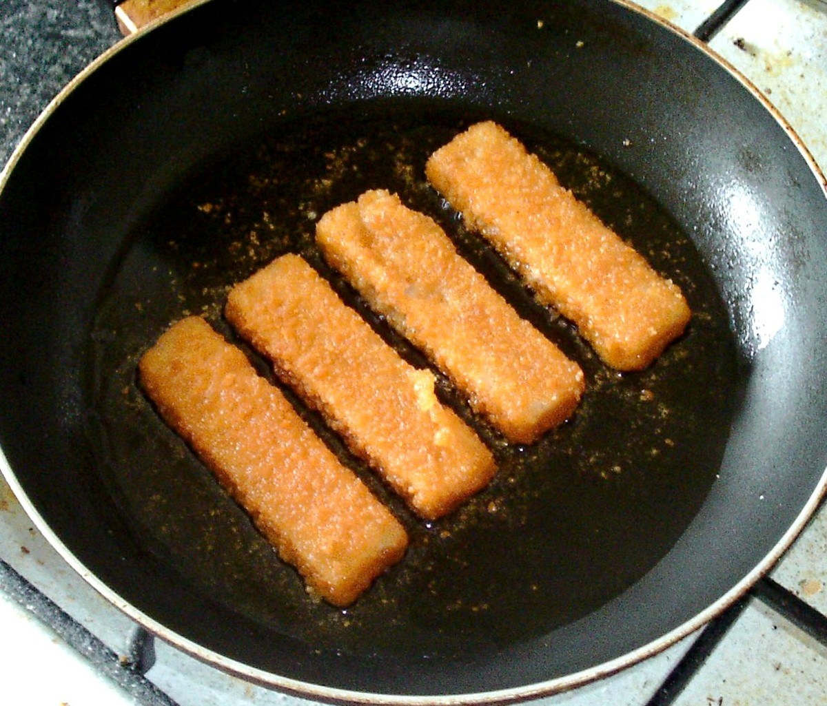 Frying fish fingers over a medium heat in a little vegetable oil.