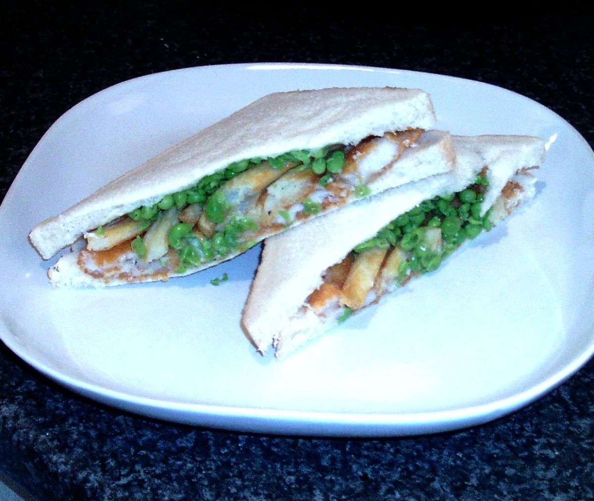 Plated and served fish fingers chips and peas sandwich