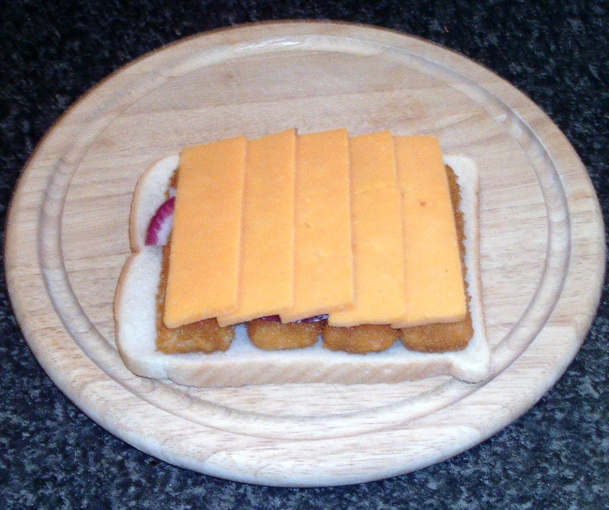 Cheese is laid over fish fingers and onion