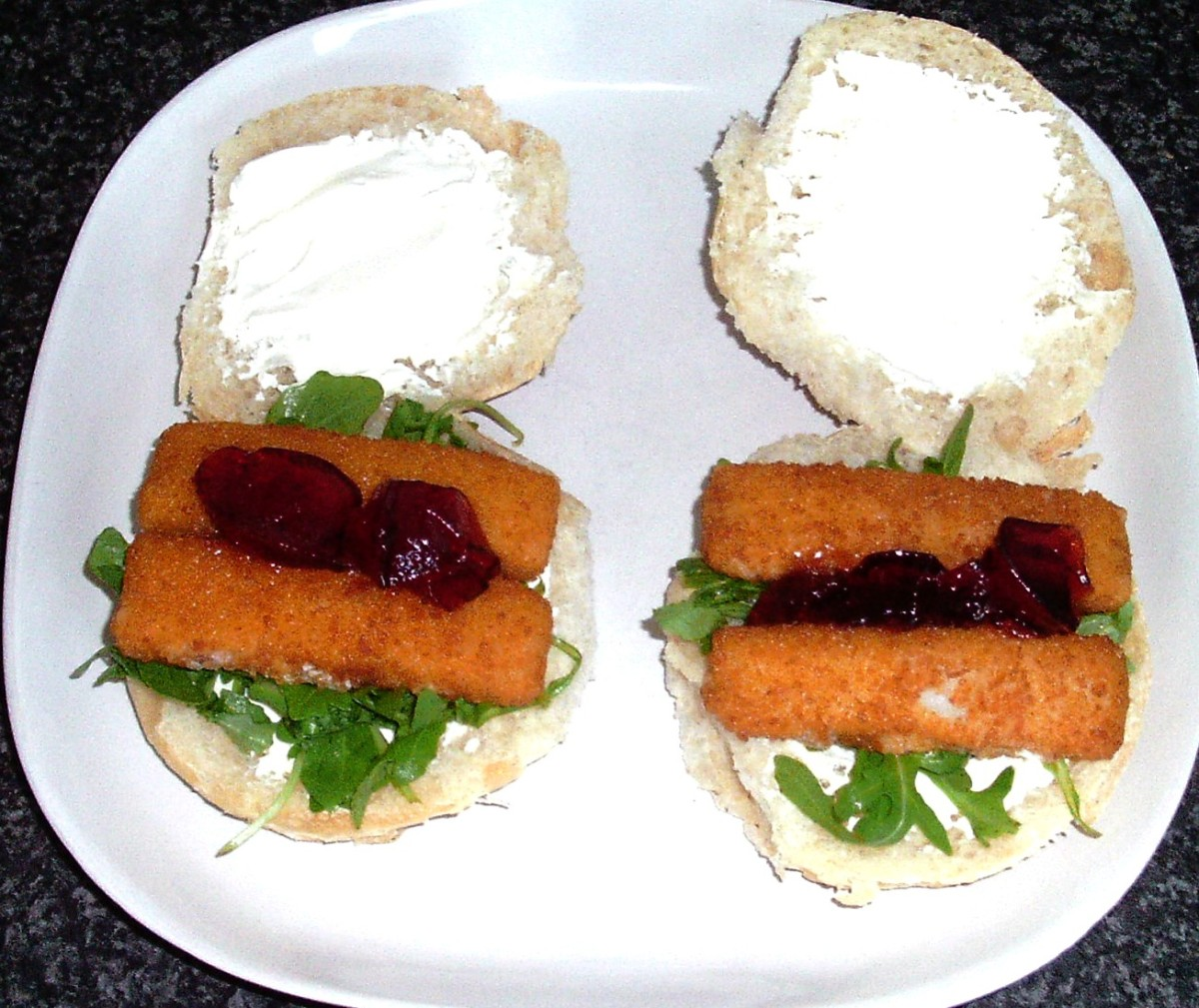 Fish fingers on rocket and cream cheese with redcurrant jelly bread rolls