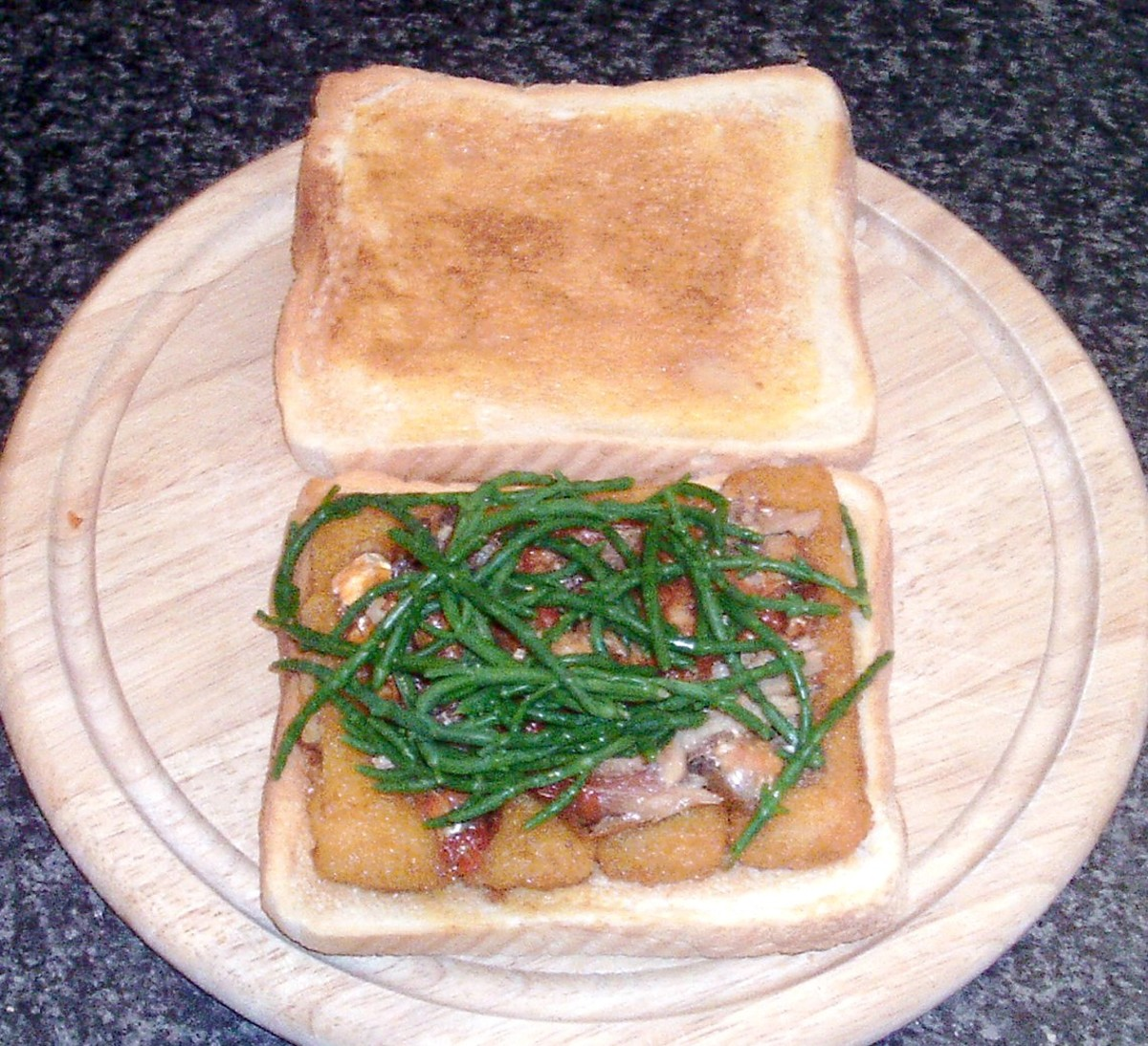 Fish fingers on toast are topped with sardines in tomato sauce and blanched samphire