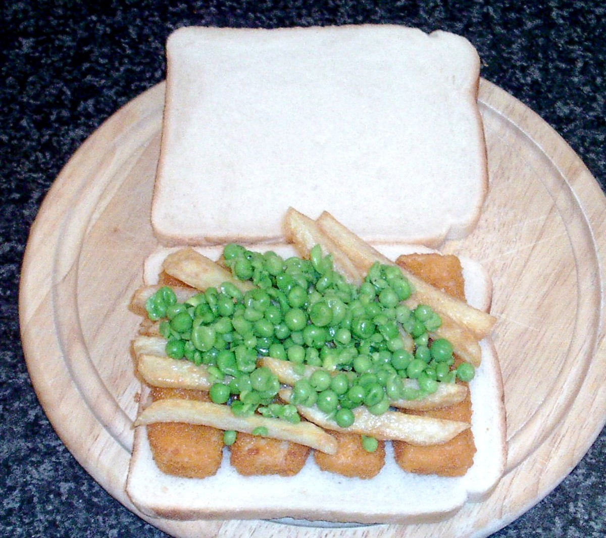Fish fingers with micro chips and peas on a sandwich