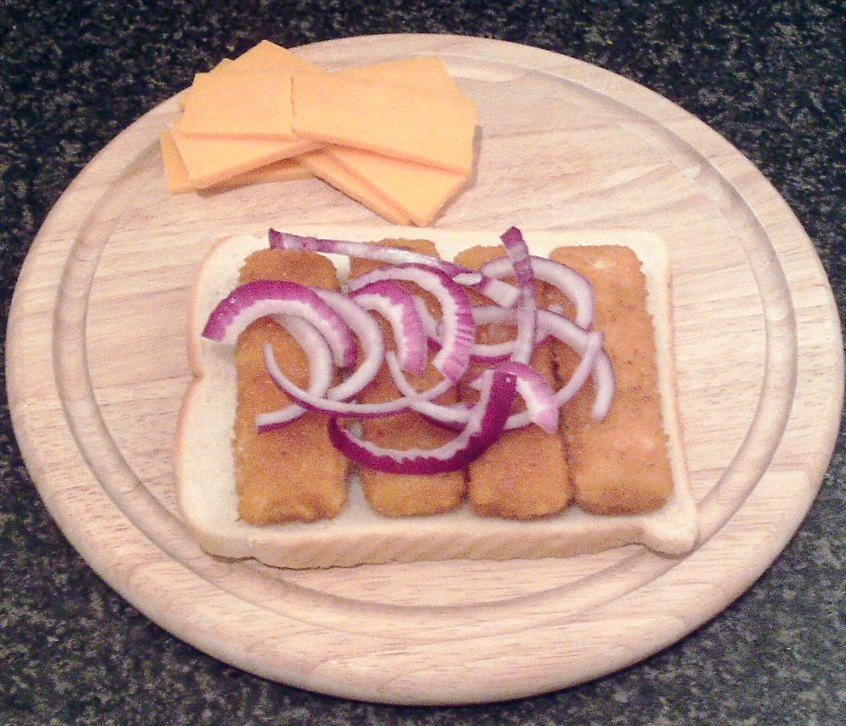 Onion strands are arranged on fish fingers on bread