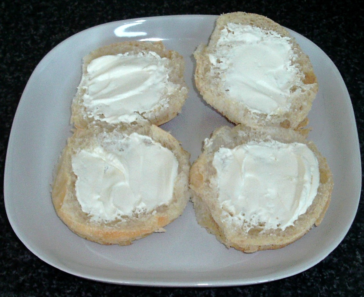 Cream cheese spread on halved bread rolls