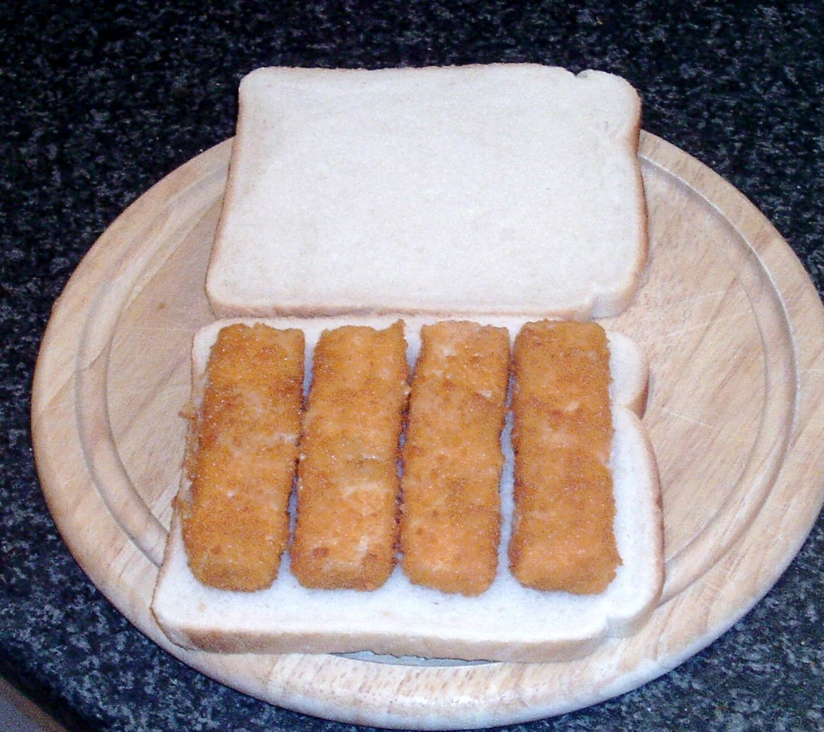 Fish fingers are laid on bottom slice of bread