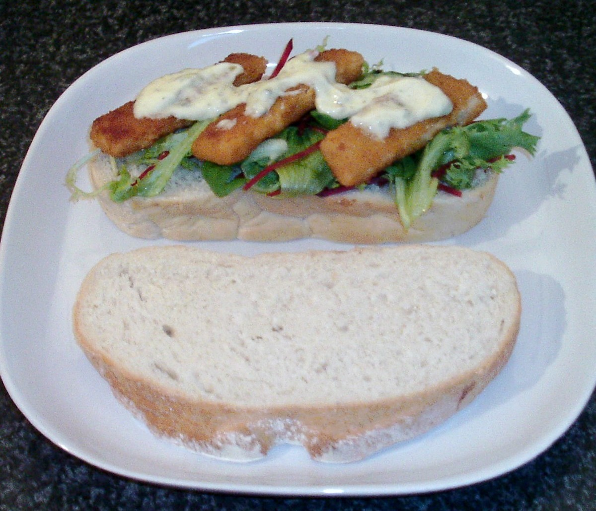 Fish fingers are laid on a crunchy mixed salad bread and spread with tartar sauce