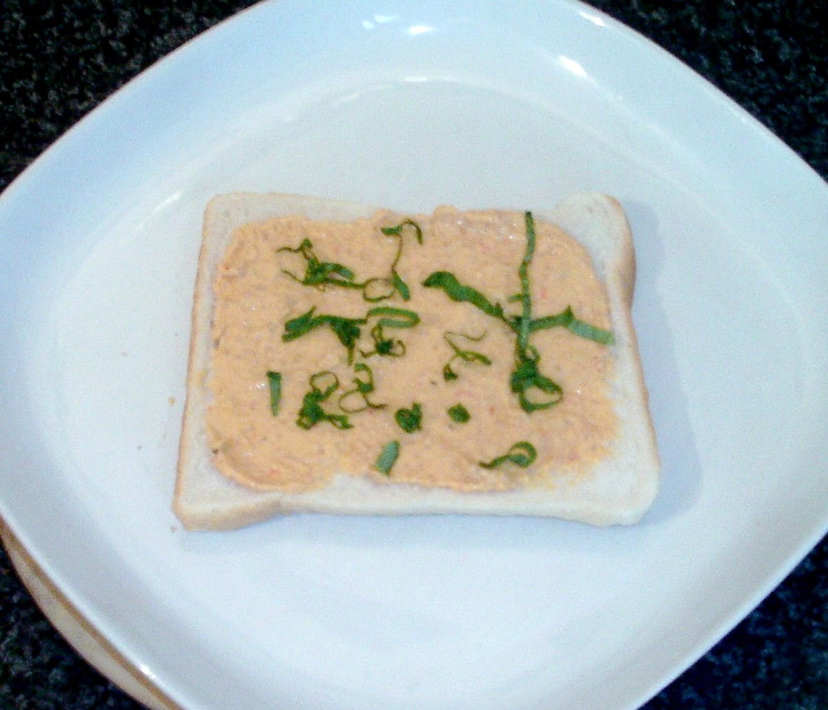 Houmous is spread on bread and garnished with shredded basil