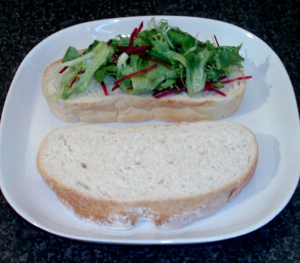 Salad leaves are laid on thick slice of bread
