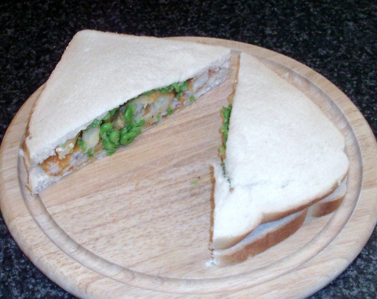 Fish fingers, chips and peas sandwich is sliced