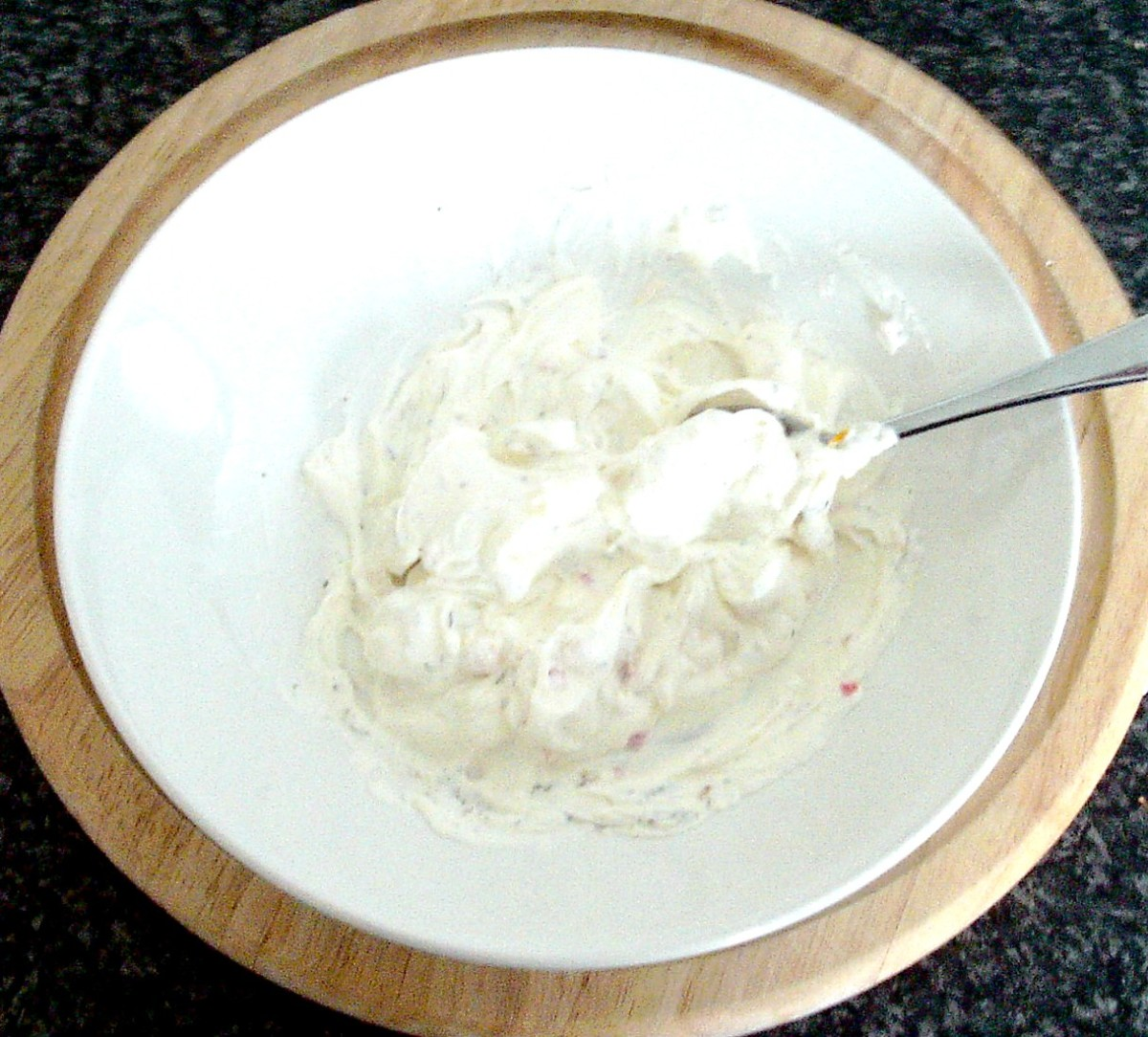 Herbs and spices are stirred in to cream cheese