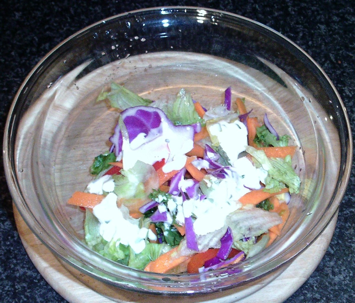 Dressing is poured over salad in a suitable bowl