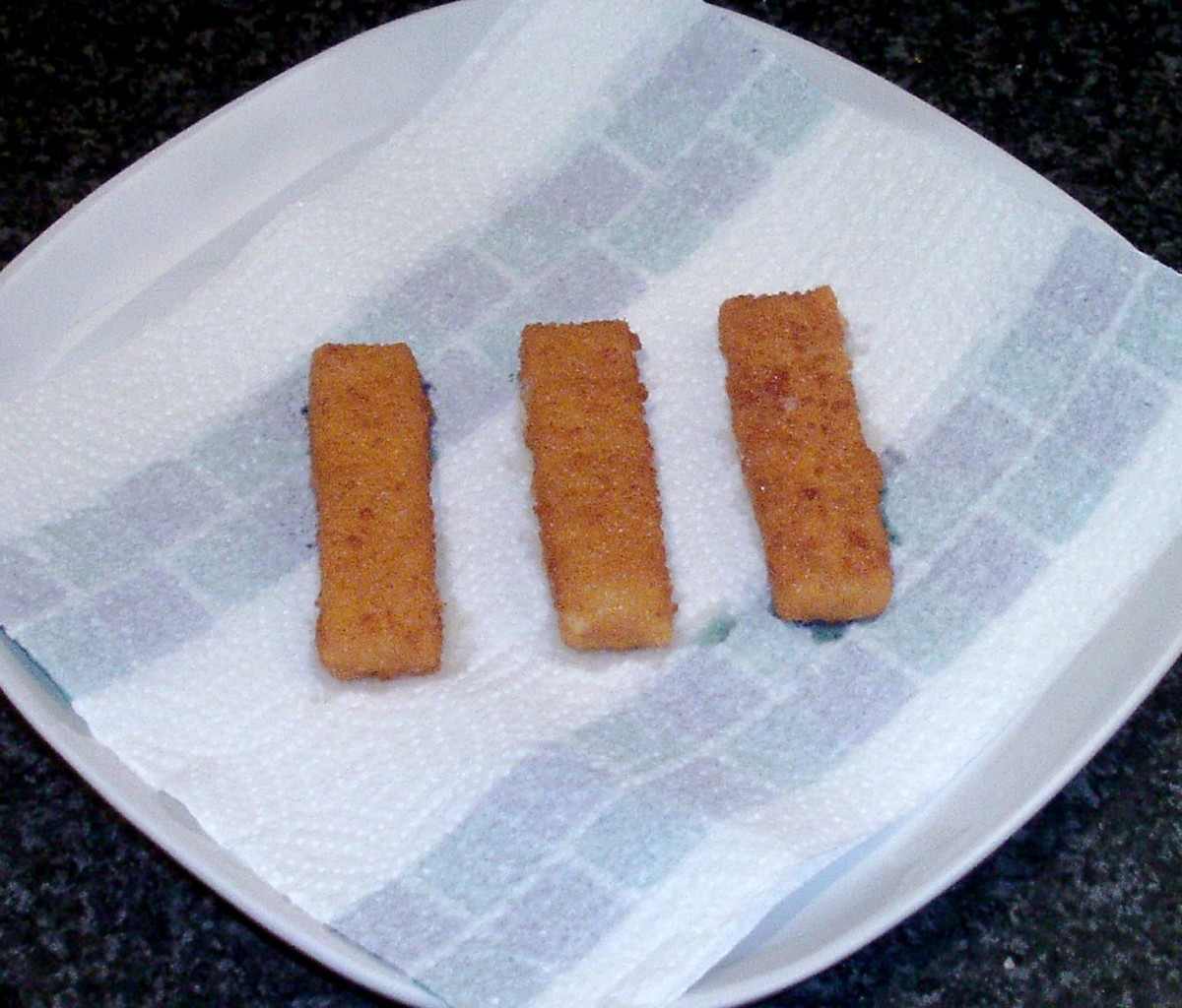 Fish fingers are drained on kitchen paper