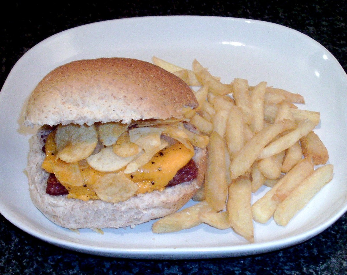 Scottish Lorne sausage and cheese on a roll with cheese and onion crisps served with fries