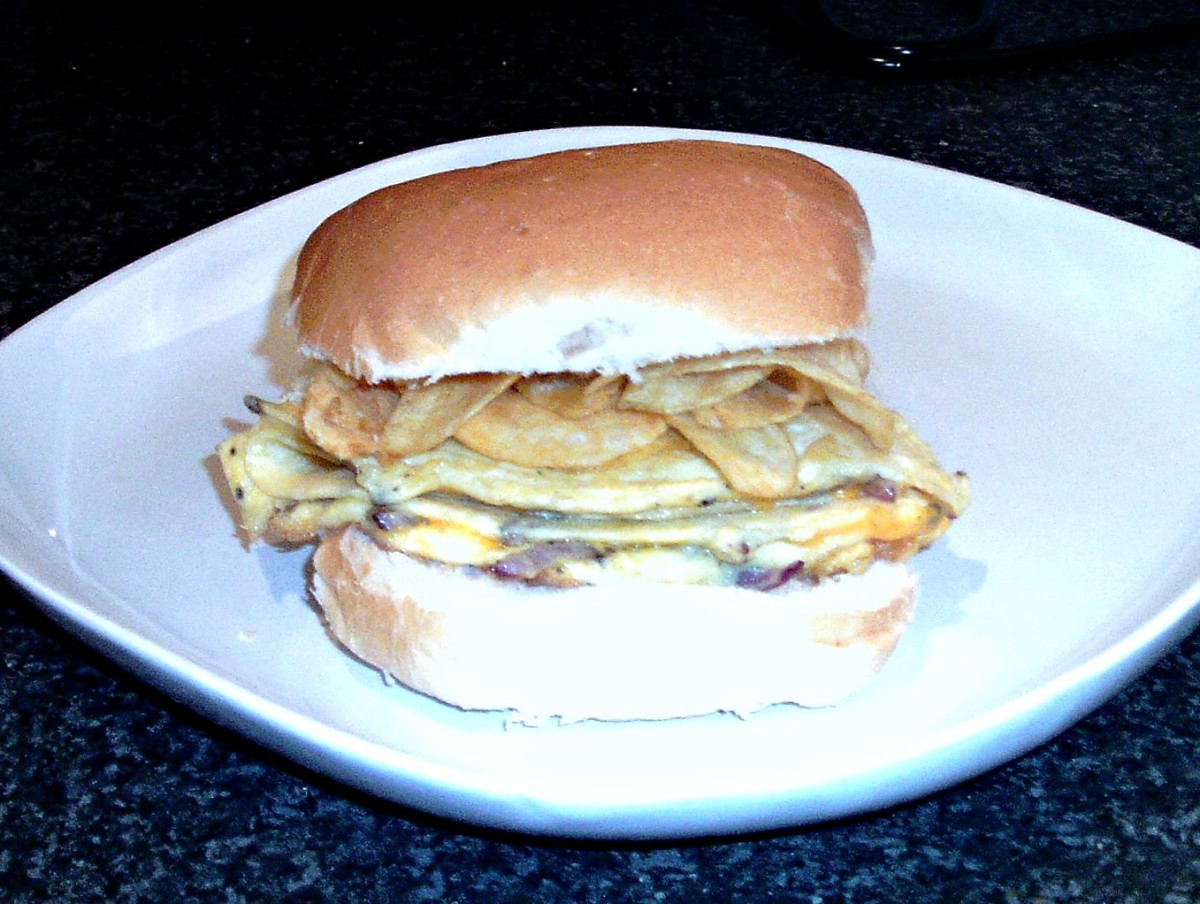 Cheese and onion omelette and crisps on a bread roll