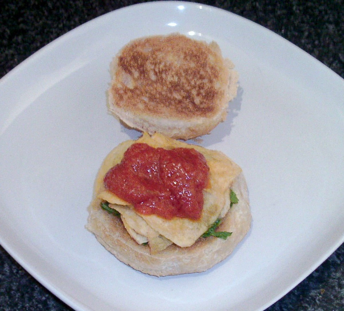 Cheese and onion crisps and rocket on a toasted roll are topped with homemade tomato sauce