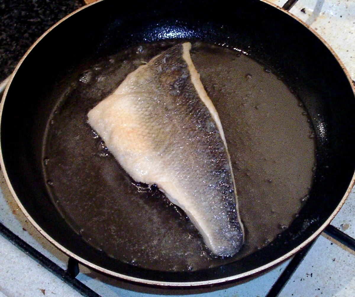 Sea bass fillet is turned to fry gently on skin side