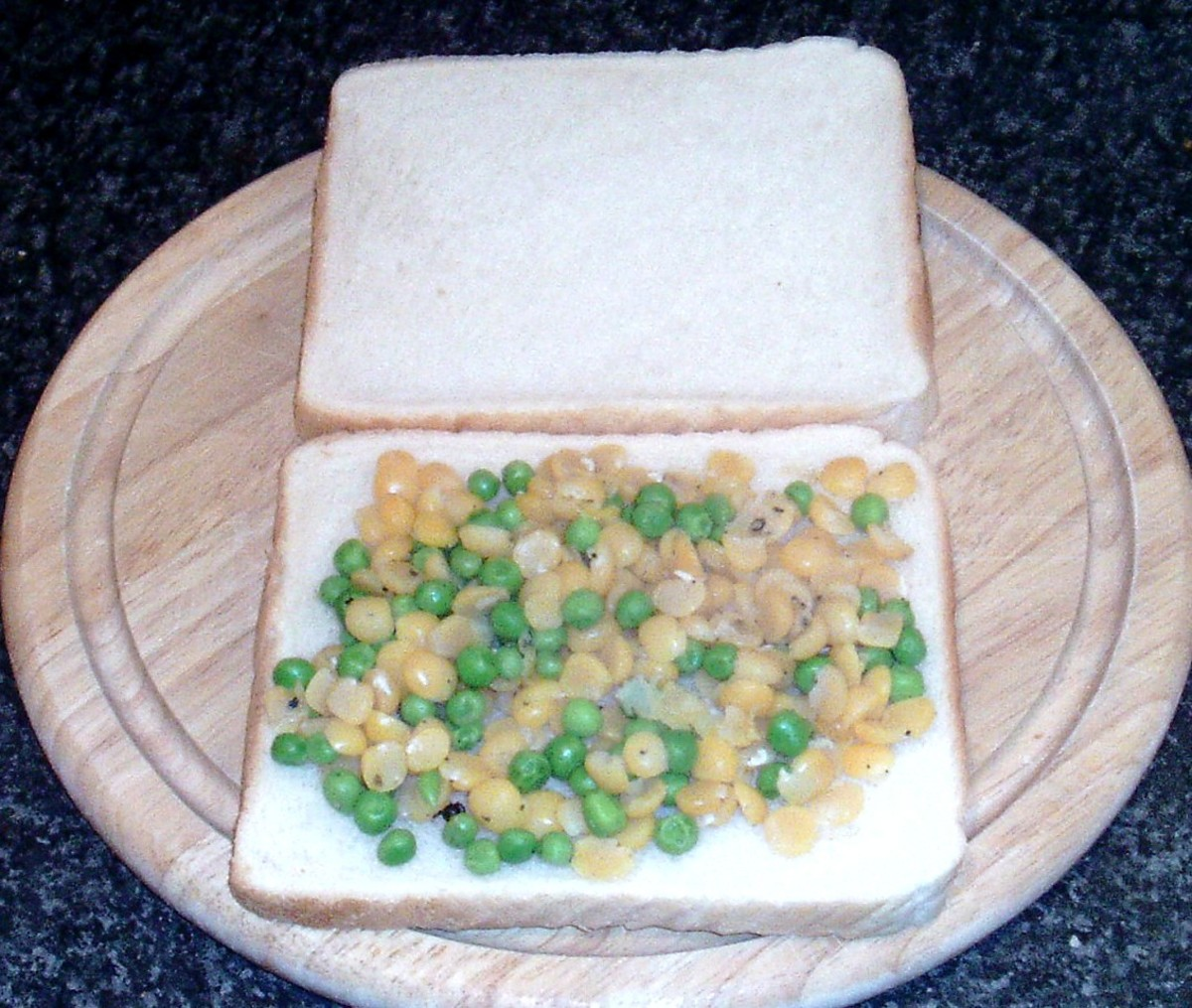 Peas are spread on bottom slice of bread