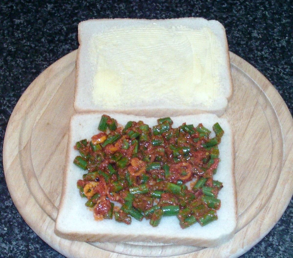 Spicy beans are spread on first slice of bread