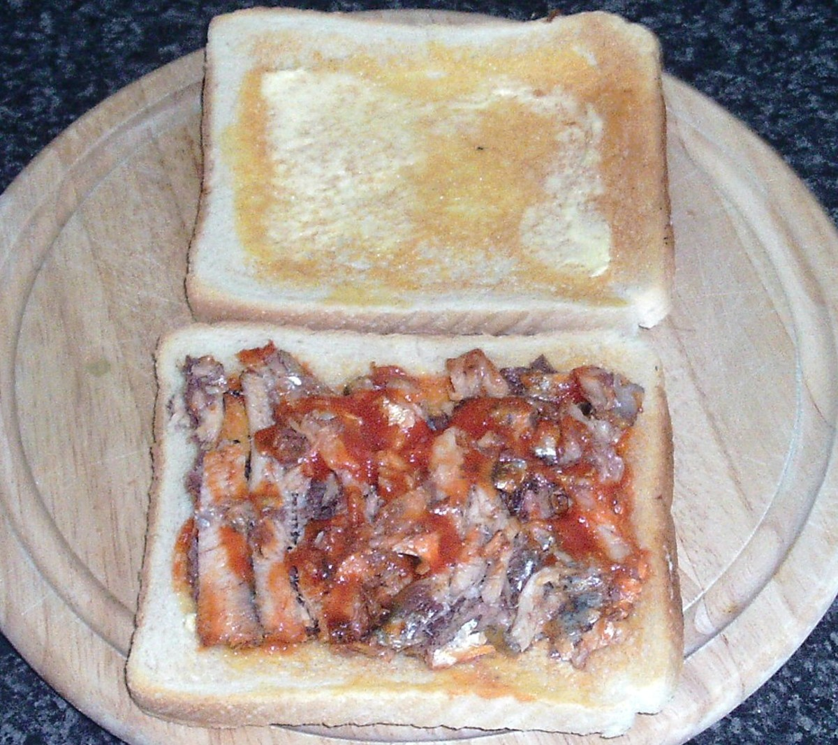 Sardines in tomato sauce are spread on toast