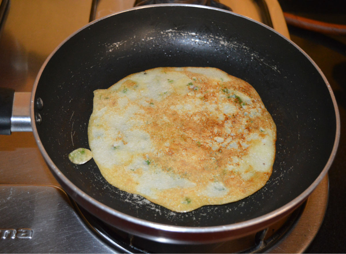 Step five: Flip it when the bottom gets golden. Add a few drops of ghee or oil on the surface. No need to cover the pan. Remove it once the other side also gets golden brown.