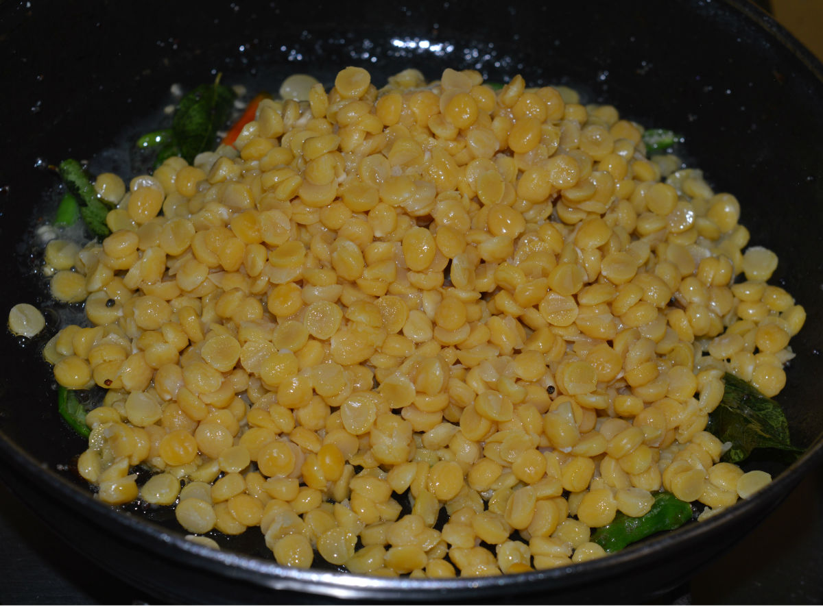 Step four: Add cooked split chickpeas. Mix them with the seasonings. Stir the mix till the water evaporates from them.