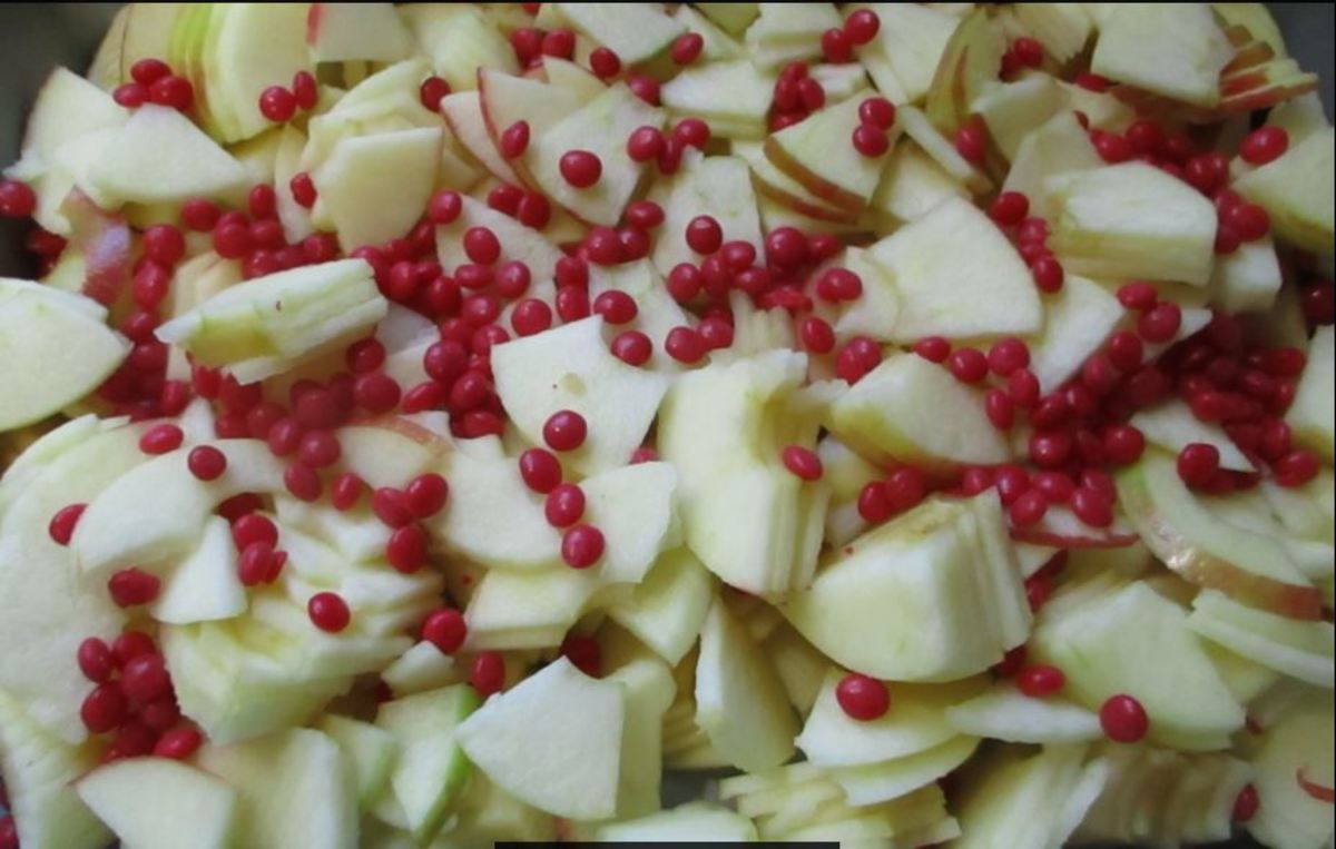 spread red hots across apples in pan