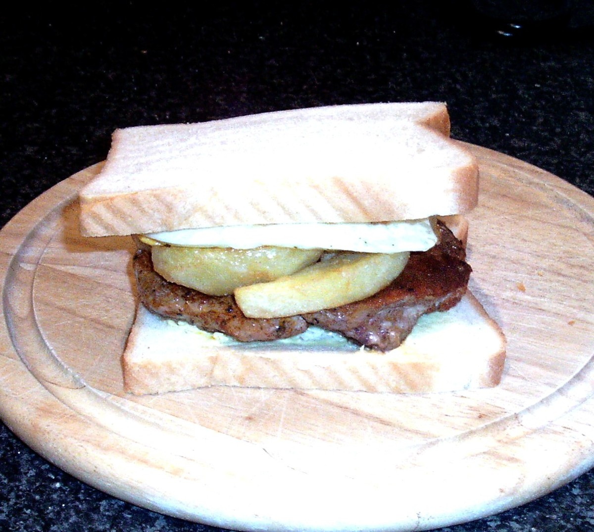 Top is placed on steak, egg and chips sandwich