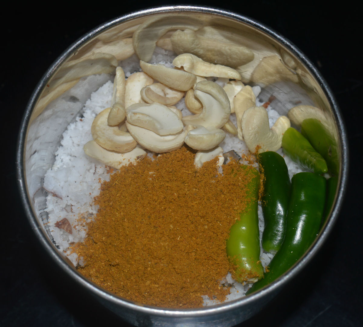 Step three: Grind grated coconut, green chilies, ginger, garlic, cashew nuts, coriander leaves, and kitchen king masala together adding water little by little to get a smooth paste.