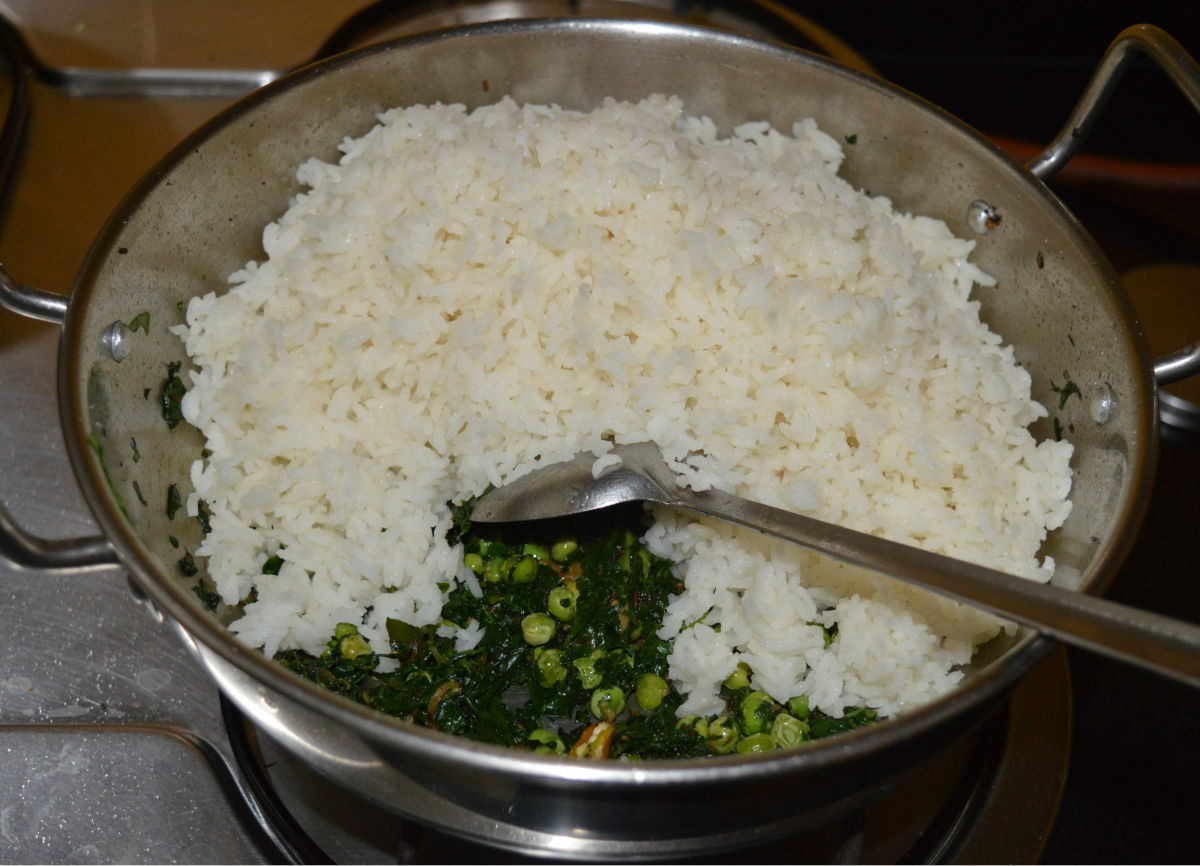 Step five: Add cooked rice. Gently mix it with the contents in the pan.
