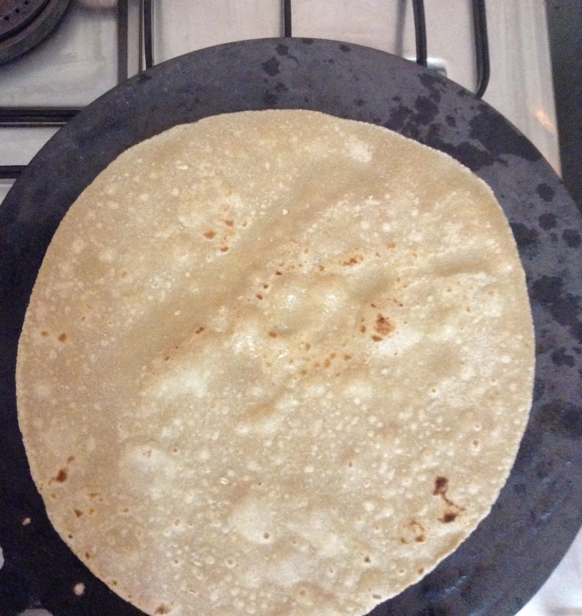 Once the Chapati starts changing color, flip it over. Let it remain on that side for a minute. Press and rotate it using a kitchen towel.